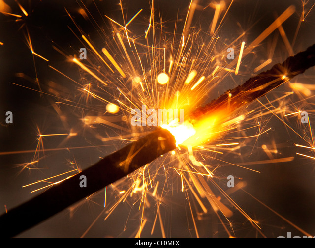 A burning sparkler firework close-up spitting sparks - Stock Image