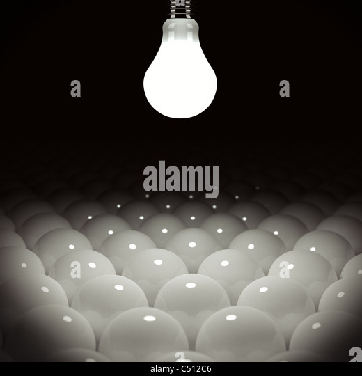 Glowing light bulb illuminating many light bulbs - Stock Image