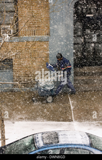 A New York City Mailman walking on the sidewalk pushing a cart whilst delivering mail and packages during a snowstorm - Stock Image
