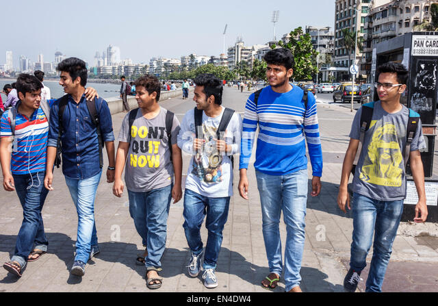 India Asian Mumbai Churchgate Marine Drive Back Bay Arabian Sea student teen boy man friends walking - Stock Image