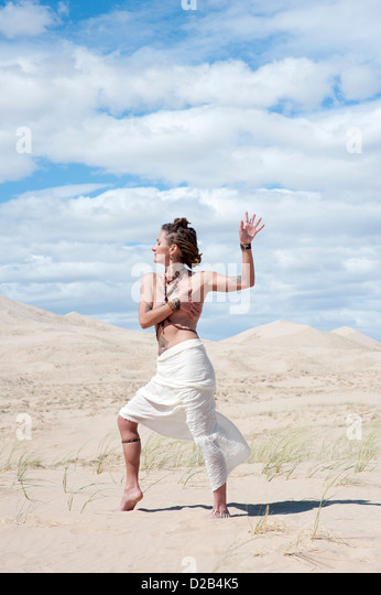 Beautiful alternative woman in a classical grecian stylesarong moving in desert dunes. - Stock Image