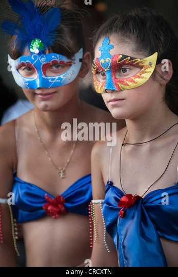 Two girls with masks at Colonia del Sacramento, Uruguay. - Stock Image