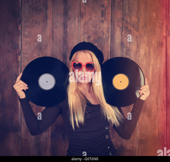 A blond hipster girl with glasses is holding two vintage vinyl record for a music entertainment concept. - Stock Image