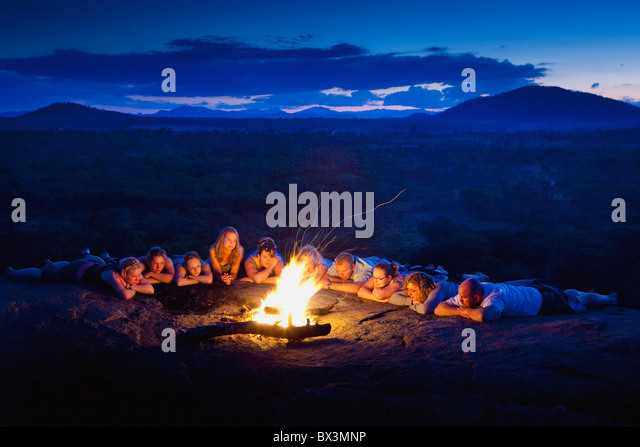 A Group Of People Laying In A Row By A Campfire; Manica, Mozambique, Africa - Stock Image