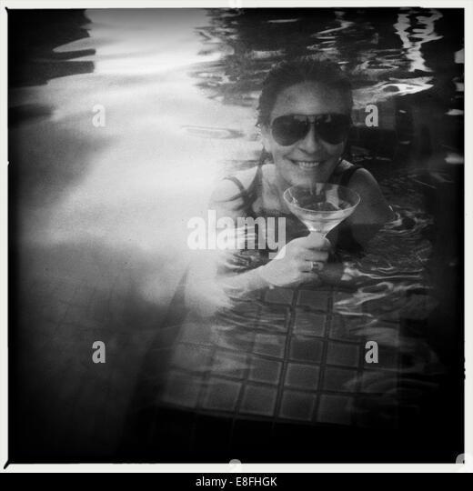 UAE, Abu Dhabi, Woman drinking cocktail in swimming pool - Stock Image
