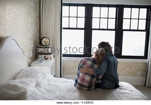 Mother hugging teenage daughter in bedroom - Stock Image