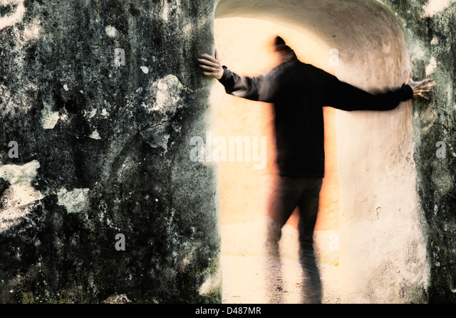Adult male moving from darkness into light through portal. He is holding on to the stone wall. - Stock-Bilder