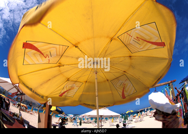 St Martin French West Indies Orient Beach Caribbean Yellow Beach Umbrella - Stock Image