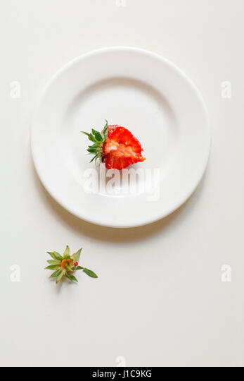 Bitten strawberry on white plate - Stock Image