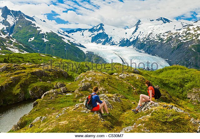 Two women hiking and enjoying the view of Portage Glacier at Portage Pass, Chugach National Forest, Southcentral - Stock Image