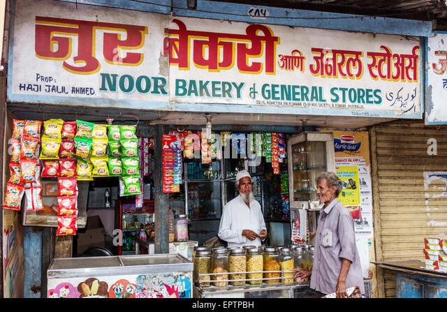 Mumbai India Asian Dharavi Shahu Nagar Road small business man Muslim owner bakery general store Hindi English sign - Stock Image