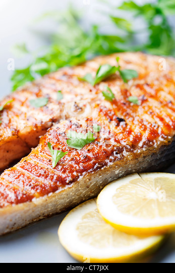 crispy grilled salmon steak with cherry tomatoes and parsley - Stock Image