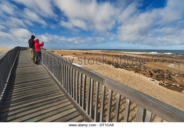 Cape Cross Namibia Tourists two people on beach walkway Cape Cross - Stock Image