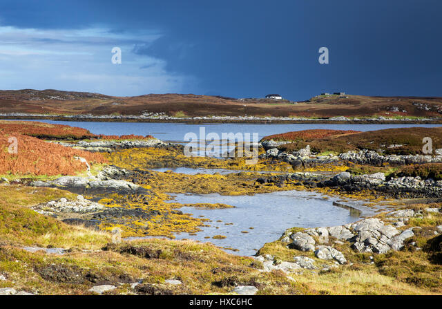 Sunny tranquil view craggy rocks and lake, Loch Euphoirt, North Uist, Outer Hebrides - Stock Image