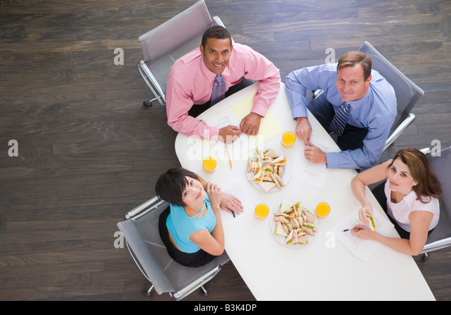 Four businesspeople at boardroom table with sandwiches smiling - Stock-Bilder