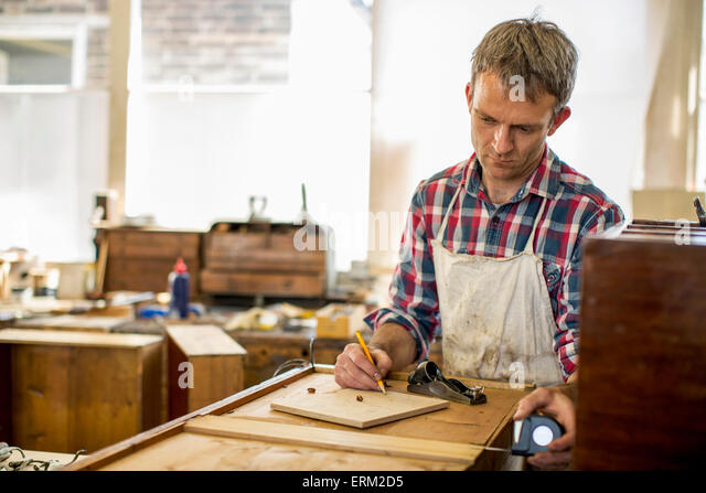 Antique furniture restorer using a pencil drawing and planning his work. - Stock Image