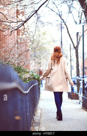 Young fashionable red head women in a camel coat walking by railings in New York city - Stock Image