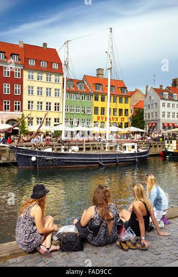 Turists relaxing at Nyhavn Canal, Copenhagen, Denmark - Stock Image