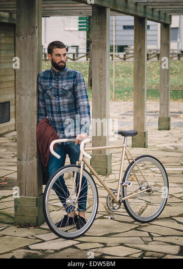 Hipster man with a fixie bike in a park outdoors - Stock Image
