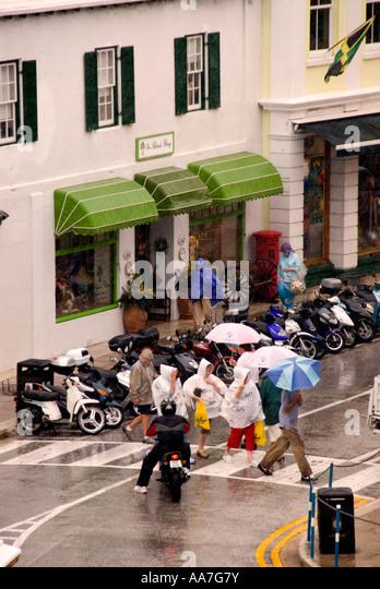 Bermuda Hamilton tourists downtown rain rainy day umbrellas raincoat - Stock Image