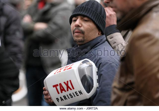 Paris, France. 14th Apr, 2017. A taxi driver holds his taxi light during a protest outside the office of Transportation - Stock Image