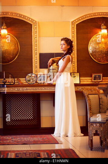 Aristocracy. Sophisticated Rich Lady standing. Orient Antique Interior - Stock Image