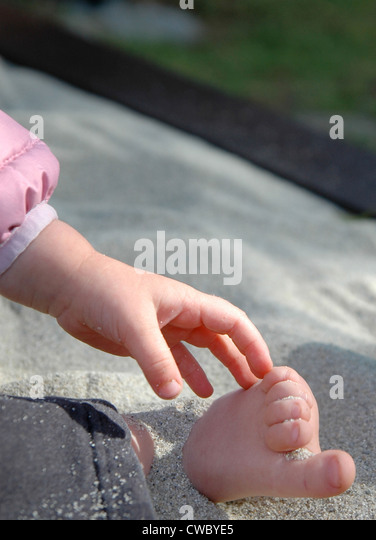 Child Touches Hand to Foot - Stock Image
