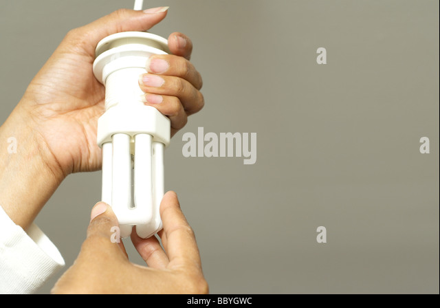 Woman's hands changing energy saving light bulb - Stock Image