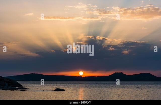 Glorious sunset and sun rays near Baya Sardinia, Sardinia, Italy - Stock Image