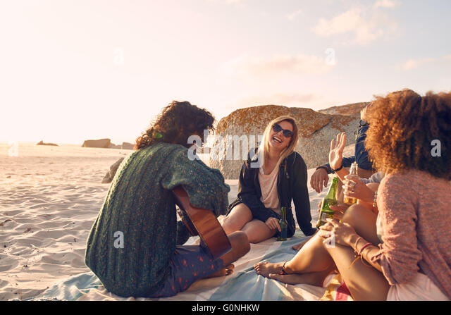 Portrait of young man playing guitar for friends. Group of friends having fun at the beach party. Young men and - Stock Image