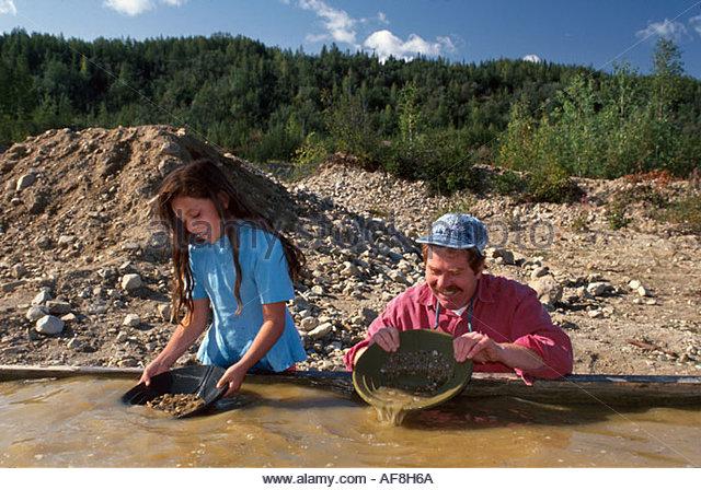 Alaska Fairbanks Old Steese Highway family panning for gold in Goldstream Creek dredge debris beyond - Stock Image
