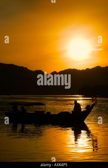 boat canoe float on water lake river reflection sun hills mountians morning sunrise evening sunset orange black - Stock Image