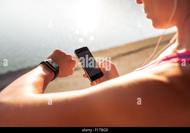 Sportswoman looking at smartwatch and holding smart phone in her other hand, outdoors. Fitness female setting up - Stock-Bilder