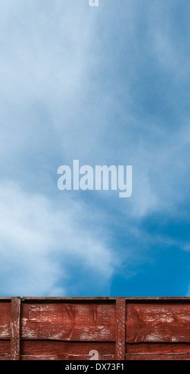 Blue sky with whispy white clouds, with red wooden fence in lower edge; tall thin. - Stock Image