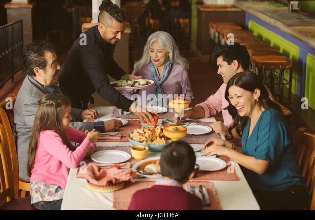 Waiter serving food to family in restaurant - Stock Image