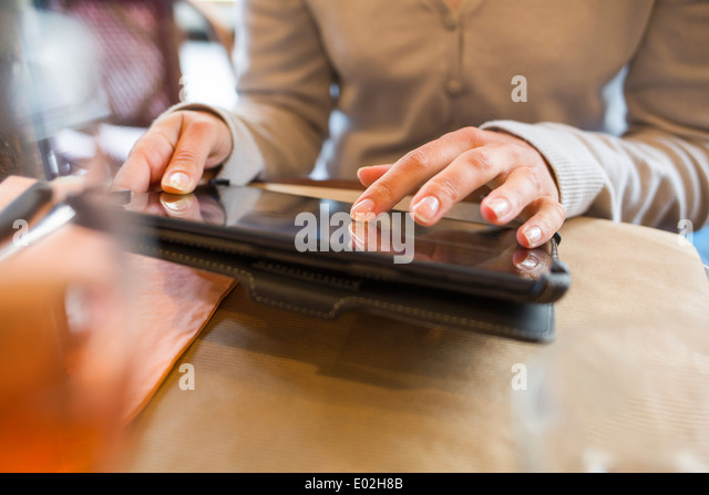 Female digital tablet computer bar restaurant - Stock Image
