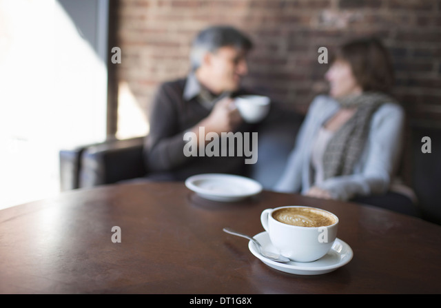 Two people sitting in a coffee shop man and woman A table with a large full cup of cappuchino coffee - Stock Image