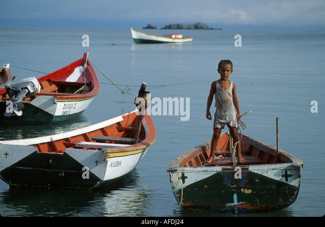 Venezuela Isla de Margarita Pampatar pinero boats fisherman's son Hispanic boy - Stock Image