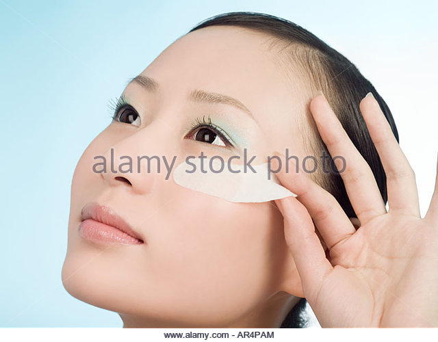 Woman removing an eye strip - Stock Image