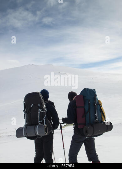 two men with heavy backpacks reading map in winter mountain landscape. Huldraheimen, Gausdal Westfjel, Norway - Stock Image
