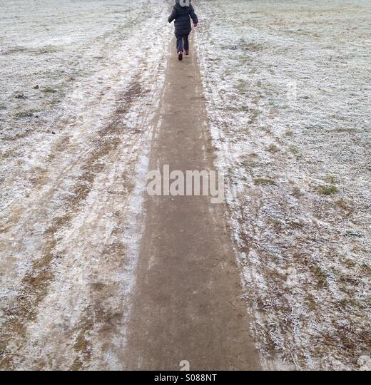 Child running frosty pathway - Stock Image