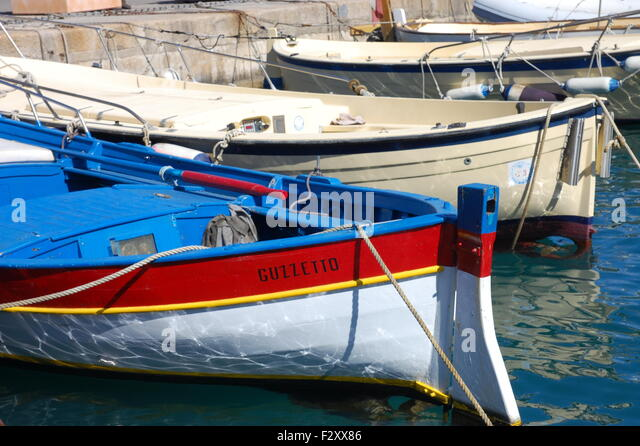 Colourful red, blue and white rowing boat in the port at Porto Santo Stefano, Monte Argentario, Italy. - Stock Image
