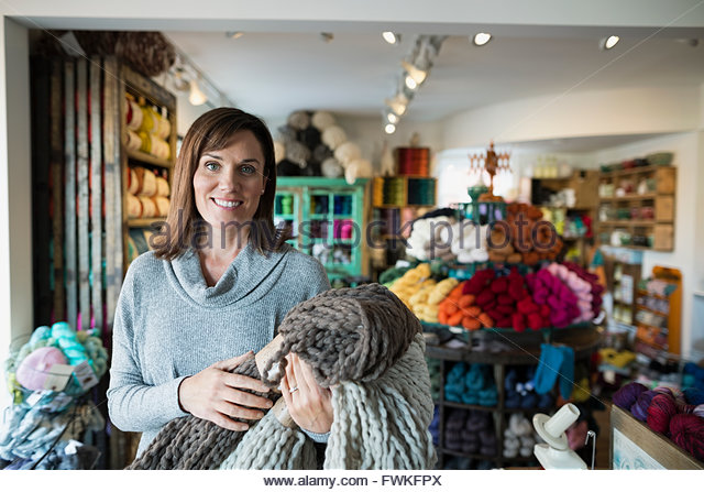 Portrait confident yarn store owner holding knitted blankets - Stock Image
