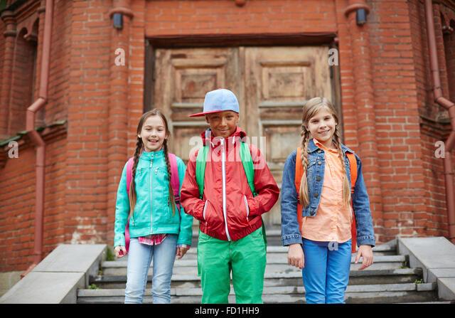 Happy schoolkids with backpacks leaving school - Stock-Bilder