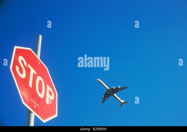Passenger jet flying over stop sign - Stock Image