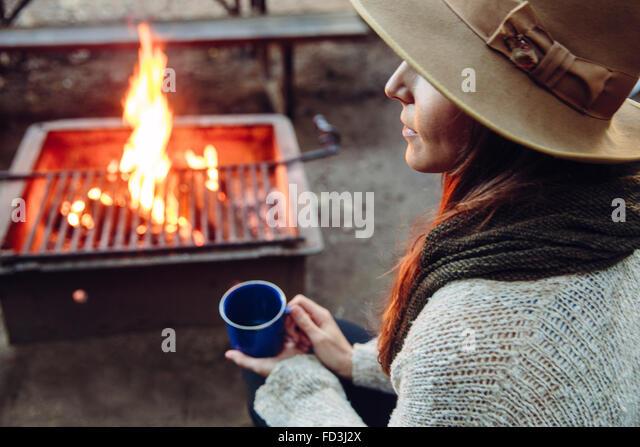 Woman enjoys a campfire moment with coffee mug - Stock Image
