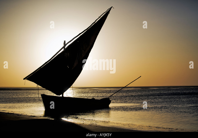 Traditional dhow or sailing boat in silhouette against the sunset off the Mozambique Coast - Stock Image