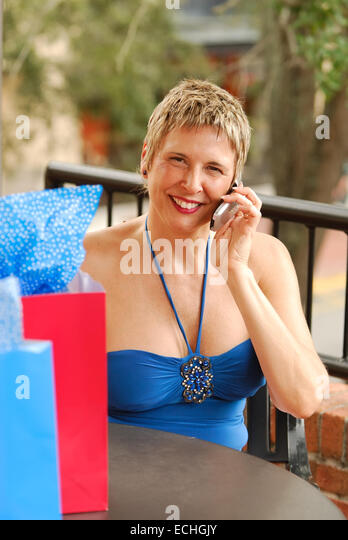 Smiling mature woman, out shopping, talking on a mobile cell phone. - Stock Image