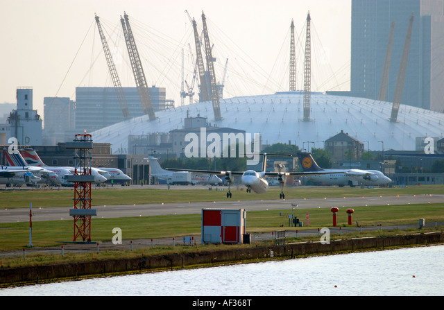 Regional turboprop plane taking off at London City Airport and Millenium Dome in the background - Stock Image