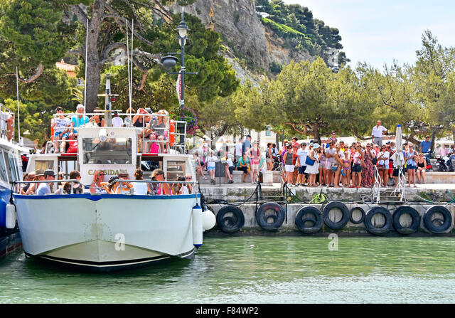 Cassis France Provence crowded harbour tourist boat awaiting departure trip to Calanque coves crowd of people waiting - Stock Image